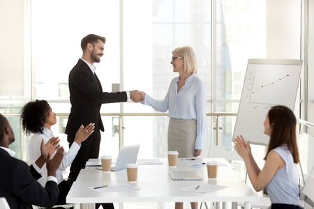 Excited confident businessman shaking hand of businesswoman at company meeting, diverse team employees applauding to successful colleague, boss congratulating subordinate with promotion or employment Stock Photo - 127862227