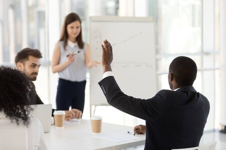 African American businessman ask question to female coach, leader at company meeting, businesswoman holding briefing, presenting new strategy, project results on flipchart, staff straining, rear view Stock Photo