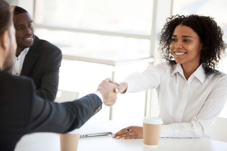 Smiling African American businesswoman shake hand of diverse colleague at briefing, employee introducing, greeting or getting acquainted business partner at company meeting, start teamwork close up