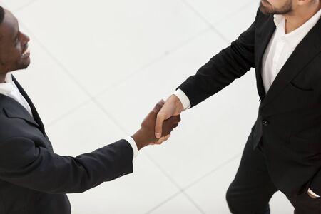 Uomo d'affari afroamericano che stringe la mano al dipendente in ufficio, partner commerciali dopo una trattativa di successo, colleghi che salutano, fanno conoscenza, congratulazioni con la promozione vista ravvicinata dall'alto