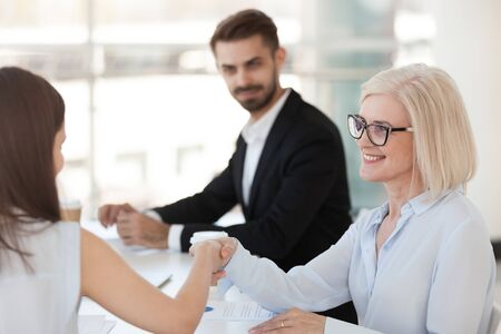 Smiling mature businesswoman shaking hand of female colleague at briefing, introducing, greeting or getting acquainted business partner at company meeting, boss congratulate subordinate with promotion