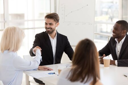 Smiling businessman shaking hand of mature woman business partner, greeting, getting acquainted at company meeting in office, colleagues handshake at briefing in boardroom, success negotiations