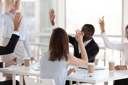 Rückansicht, Mitarbeiter, die an Teambuilding-Aktivitäten beteiligt sind, erhobene Hände, reife Trainerin, Mentorin mit Geschäftsbriefing, Mitarbeiterschulung, Geschäftstrainer interagieren mit verschiedenen Büroangestellten