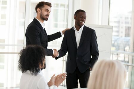 Confident businessman shaking hand of African American business partner at business meeting, successful negotiations, boss congratulate subordinate with promotion, introduce new worker to colleagues Stock Photo - 127862315