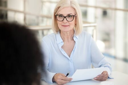 Confident mature businesswoman hold paper document, listen to colleague talk at company meeting, employees discuss project result, report, marketing plan, interview with intern in office close up Banque d'images - 127862316