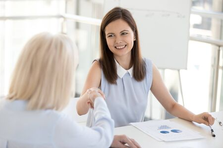 Smiling happy businesswoman greeting, shaking hand of colleague at company meeting, female employee introducing, getting acquainted with business partner, client, congratulate with promotion close up Stockfoto
