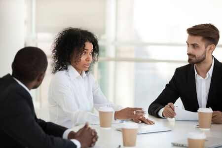 African American businesswoman discuss project with diverse team at company meeting, female boss explain business strategy, marketing plan, share thoughts, interested employees listen to colleague Banque d'images - 127862379