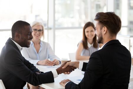 Smiling African American businessman greeting, shake hand of male colleague at business briefing, employee introducing, getting acquainted business partner at company meeting, negotiates, respect