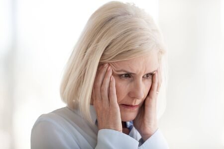 Mature frustrated businesswoman suffering from headache or panic attack, middle-aged female employee touching, massaging temples, feeling pain, dizzy, tired of difficult office job, close up