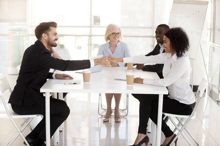 Smiling business partners handshaking, closing deal at meeting in office, African American businesswoman shake hand of excited businessman, having successful negotiations, start work together