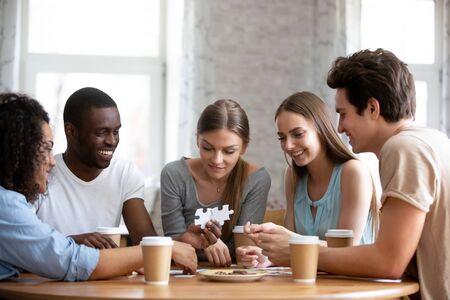 Involucrados interesados felices sonrientes amigos de raza mixta sentados juntos en la mesa, tomando café y armando rompecabezas, pasando el fin de semana juntos, concepto exitoso de trabajo en equipo.