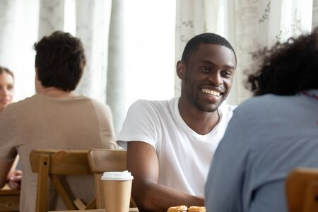 Happy smiling african american guy sitting in coffeehouse with biracial female friend or attending speed dating event, enjoying meeting new interesting person, laughing, romantic relations concept. Фото со стока - 127862709