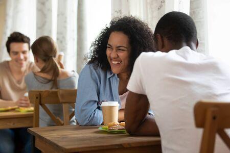 Gelukkig jong gemengd rasmeisje dat speeddating bijwoont, kennis maakt met interessante mensen, grappen maakt, lacht, plezier heeft. Duizendjarige vrouw ontmoet zwarte vriend, geniet ervan om samen tijd door te brengen.