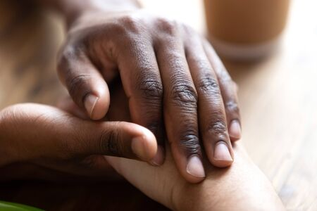 Close up african american male holding young beloved female hands, showing tenderness, love, support. Romantic relations moment, mixed race couple dating, sincere feelings or apologizing concept. Stock Photo