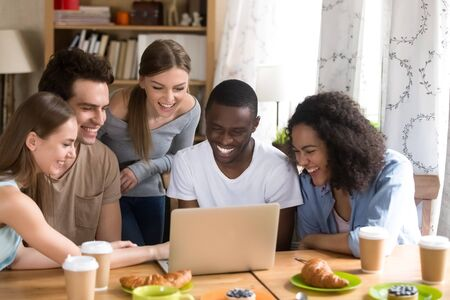 Happy company of diverse male and female young friends sitting at table in cafe with computer, laughing at funny videos or comedy movie using wifi, watching party photos, enjoying free time together. Stok Fotoğraf