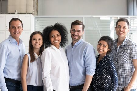 Smiling diverse office workers group, multiracial team of employees looking at camera, motivated successful business people, staff posing together in modern office, multi-ethnic colleagues portrait Stock Photo