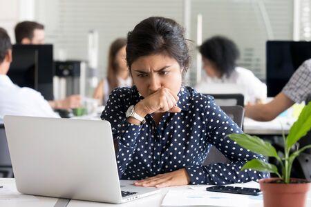 집중적으로 걱정하는 인도 여성 사업가가 노트북 화면을 보고, 의심하고, 어려운 질문이나 작업에 대해 생각하고, 나쁜 소식을 듣고 화가 난 여성 직원, 피곤한 회사원은 너무 많은 일을 합니다