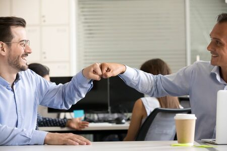 Friendly smiling male colleagues fist bumping at workplace, happy coworkers sharing success, middle-aged men celebrating good teamwork result, satisfied by collaboration, cooperation at work, close up