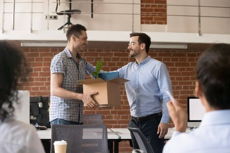 Friendly company ceo welcoming new male employee holding cardboard box with belongings in hands, first day at work, team welcoming new member, newcomer, getting acquainted with coworkers, introduction Фото со стока