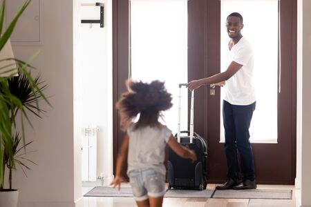 Rear back view small african daughter running to meet beloved loving father returned arrived from travel business trip standing in doorway with luggage baggage. Welcome back and family reunion concept