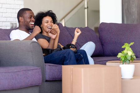 Cheerful black couple sitting on couch in living room celebrating relocation at new modern first house family feels excited and proud raising hands in yes gesture. Happy homeowners, moving day concept