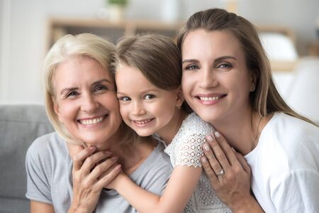 Head shot of three diverse generations indoors. Portrait of beautiful little granddaughter daughter and grandmother smiling looking at camera sitting together on couch hugging in living room at home