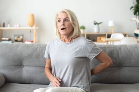 Unhappy attractive senior woman suffering from back pain sitting alone on sofa in living room at home. Middle aged female has severe sharp pain touching rubbing lower back feels worried and frightened