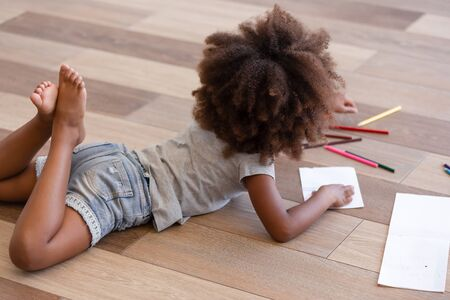 Side rear view afro kid little daughter lying on warm wooden floor in living room at modern home wearing summer clothes barefoot draws on paper with colored pencils. Weekend leisure activities concept