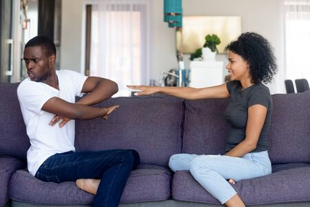 African black spouses quarrelling sitting on couch at home, wife repent make excuses apologizing angry husband refuse listen her. Mistakes cheating problems in relationship, break up and split concept Stock Photo