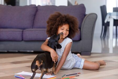 Preschool african girl distracted from drawing playing caressing dachshund puppy on warm floor with parent in living room having fun at home, modern house, best friend for kid, family with pet concept