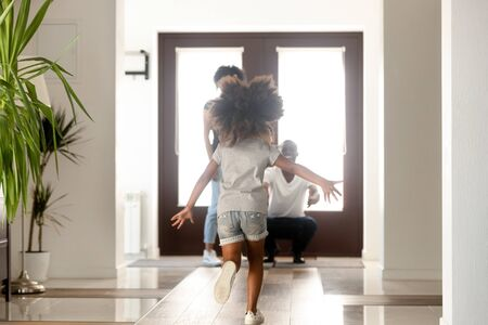 African family having fun in hallway, daughter missed her parents running to mom and dad standing in the doorway of modern house. Family reunion, mortgage happy homeowners arrived a new home concept