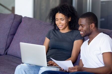 African married couple sitting on sofa at home use laptop holds paper check bills, online bank account balance feeling satisfied and happy. Refund or income, last loan lease payment good news concept 스톡 콘텐츠 - 127863322
