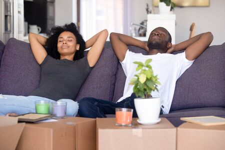 African couple put hands behind head rest on sofa with closed eyes big boxes with stuff, breath fresh air take break on moving day into new first home. Property buyers or easy delivery service concept