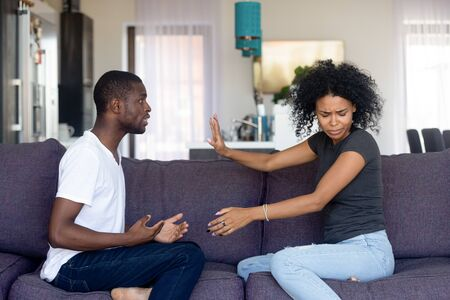 Black unhappy couple having quarrel at home arguing sitting on sofa in living room at home, husband makes excuses wife refuses listen dont believe him. Cheating, problems, fed up and break up concept
