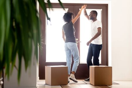 African couple feels happy entering at new home dancing near big cardboard boxes with belongings celebrate moving day standing at doorway. First time house buyers loan or fast delivery service concept