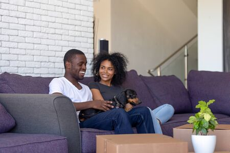 African couple wife husband resting on sofa with dachshund dog in living room on moving day delivered boxes with unpacked belongings. Buyers of first house, loan mortgage relocation, new life concept