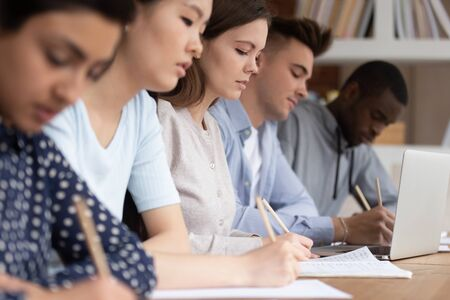 Multicultural diverse students sit at shared desk making notes studying together at university, multiethnic mixed school group write listen to tutor teacher talk giving lecture at college or school Imagens