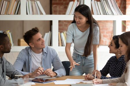 Motivated Asian female team leader stand hold meeting with mates talk discuss project or assignment, focused young ethnic girl speaker or tutor speak with students at group gathering. Teamwork concept Stock Photo