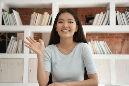 Happy Asian young female sit at desk waving to camera say hello to viewers shooting vlog or video, smiling ethnic girl greeting talking having conversation or videocall at laptop