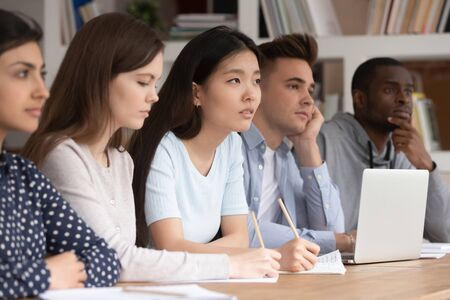 Attentive multicultural diverse young people sit at desk listen to teacher talk giving lecture or explaining material, concentrated multiethnic students make noted write down during lesson at college Stock Photo