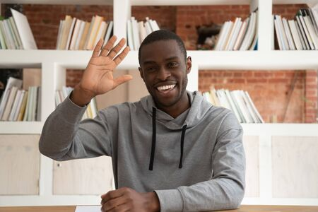 Happy african American guy sit at desk wave having video call or online conversation, smiling biracial male blogger or coach shoot live tutorial or training course greet with viewers Reklamní fotografie - 127893416