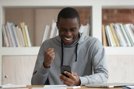 Excited african American man sit at desk holding smartphone feel euphoric winning online game on gadget, happy black male student receive pleasant email, pass exam or get college grant