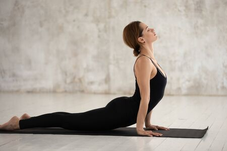 Woman in black sportswear performs yoga doing Urdhva Mukha Svanasana or Upward Facing Dog pose working out indoors studio shot, side view, healthy lifestyle physical mental spiritual practice concept