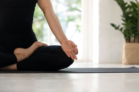 Close up cropped image view womans legs in black sporty pants sitting in lotus pose fingers folded I mudra gesture on mat indoors, female do meditation breathing feels no stress anxiety relief concept Stock Photo