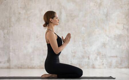Seitenansicht ruhige Frau in schwarzer Sportkleidung gefalteten Palmen macht Namaste Geste Seiza Übung Vajrasana Asana gegen strukturierten beige Grunge Wand Studio Hintergrund, Vorbereitung auf Meditationshaltung