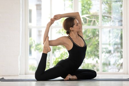 Young woman wear black sportswear practising yoga indoors, window view of green trees sunny morning, girl performing Mermaid Pose or Eka Pada Rajakapotasana asana, physical mental health care concept