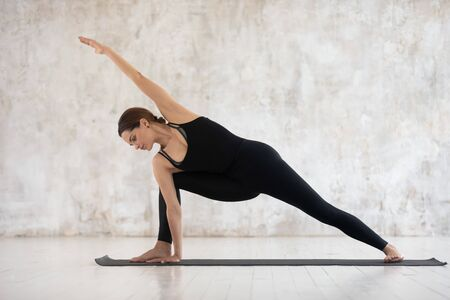 Full-length young woman wear black activewear doing Utthita Parsvakonasana asana or Extended Side Angle pose standing on mat, practising yoga exercises indoors, physical practice mental health concept