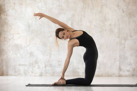 Slim woman in black active wear doing Half Camel Posture Ardha Ustrasana on mat practice yoga against beige grunge wall studio background, connect body and mind physical and spiritual activity concept Stock Photo