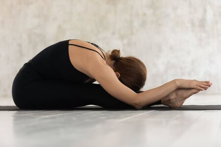 Young sporty woman wearing black shirt and leggings clothing performing Paschimottanasana exercise Seated Forward Bend pose side view, do asana on mat, practising yoga, mental physical health concept