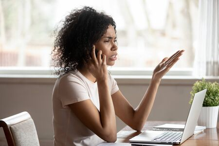 Irritated mixed race 30s woman sit at table near laptop gesticulating feels indignant having difficult conversation by mobile phone, businesswoman solve problems distantly discussing business issues